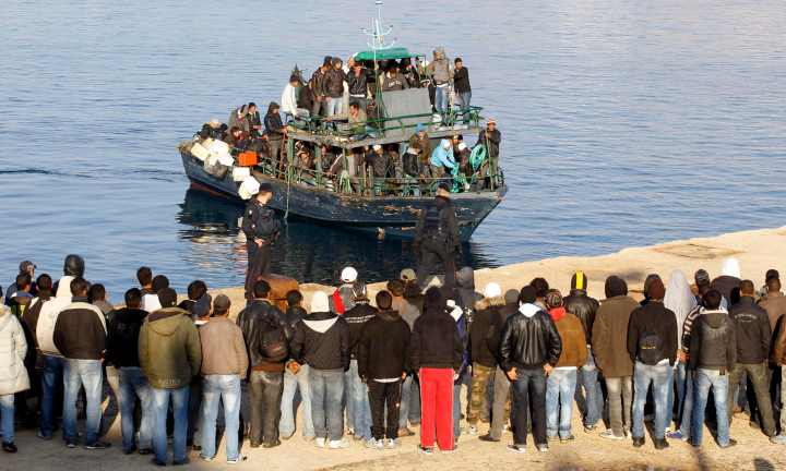 Migrants from North Africa arrive, escorted by Italian Guardia di Finanza, at the southern Italian island of Lampedusa in this March 24, 2011 file picture. Thousands of Eritreans attempt each year to make a trip to reach Europe, fleeing one of Africa's poorest and most isolated nations, a place where army conscription with pitiful pay can last years. Many die on the trek. Probably all of the more than 360 migrants who drowned in a shipwreck near Italy's coast in October 2013 were Eritrean, though many are still unidentified. To match Feature ETHIOPIA-ERITREA/MIGRANTS. REUTERS/Alessandro Bianchi/Files (ITALY - Tags: SOCIETY IMMIGRATION)